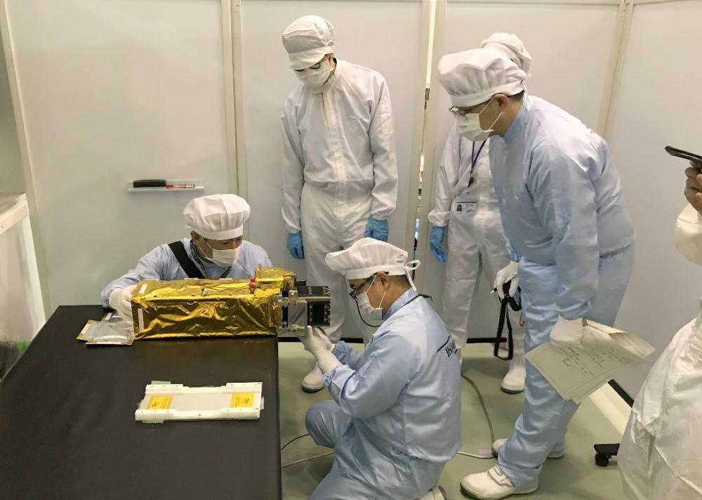 Các chuyên gia Nhật Bản lắp đặt vệ tinh NanoDragon của Việt Nam vào ống phóng của tên lửa.
