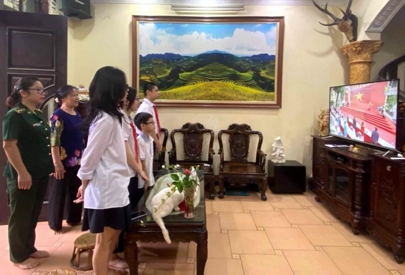"""Các học sinh và phụ huynh trang nghiêm cử hành nghi thức Chào cờ trong """"Ngày hội đưa trẻ đến trường"""" trên tivi"""